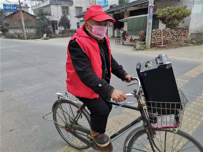 志愿者骑着自行车、待着音响宣传疫情防控知识.jpg