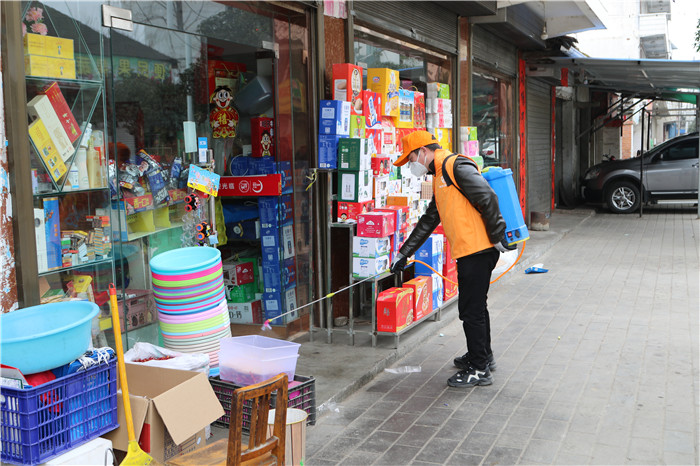 梁山镇石拱社区新时代文明实践志愿者在超市等人口密集处进行消毒作业.jpg
